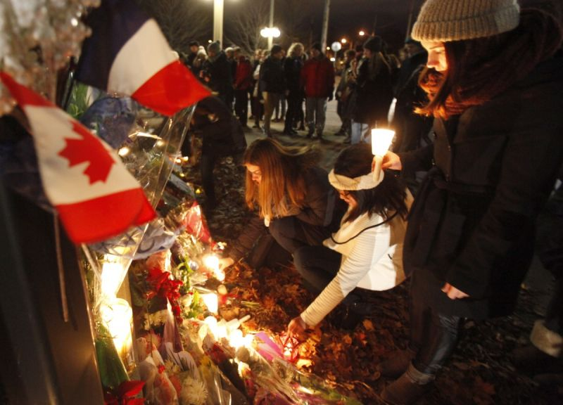 Mourners lay flowers in front of the French Embassy in Ottawa. Photo: Getty
