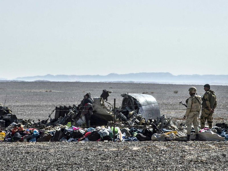 Egyptian soldiers stand guard next to debris and belongings of passengers of the plane.
