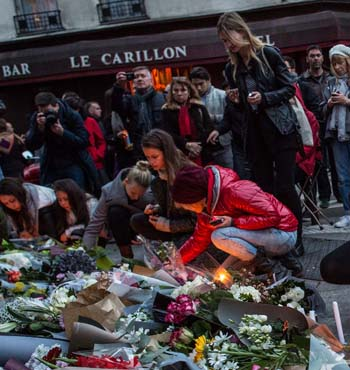 Mourners leave candles in front of the Petit Cambodge restaurant near Le Carillon restaurant where attacks took place.