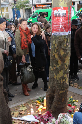 Two women cry together at a makeshift memorial for those who died in the Paris terror attacks. Photo: AAP