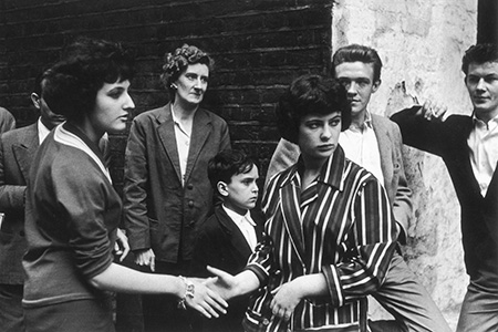 Soho teenagers in typical late 1950s attire of suits, striped jackets and pullovers meet and greet each other on the street Date: 1959