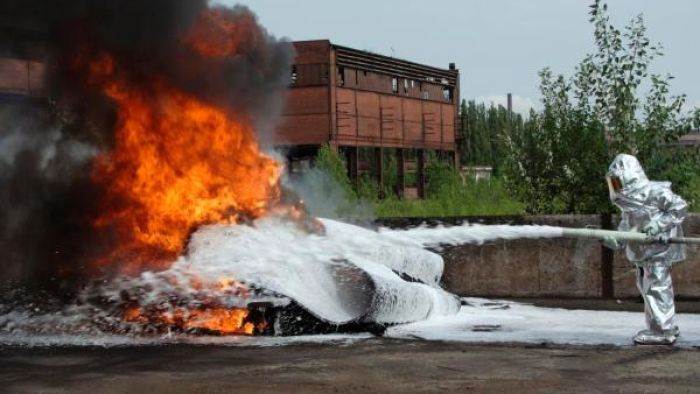 Firefighting foam, shown here in a controlled test, has prompted warnings against eating fish from certain Brisbane waterways.