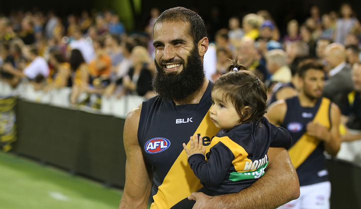 A grinning Houli brings his daughter onto the ground after beating Brisbane in round 18. Photo: Getty