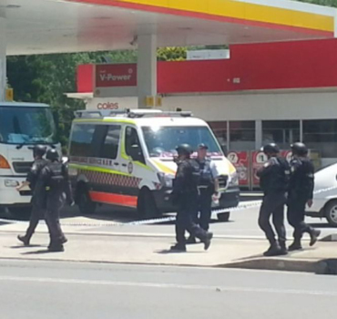 Heavily armed police patrol the Shell service station.