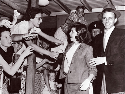 SYDNEY, AUSTRALIA: Legendary US singer Frank Sinatra (r) in a picture taken 21 January 1955 in Sydney arrives with his daughter Nancy14, at the airport while eager fans almost spill over the fence in their efforts to get autographs. Frank Sinatra, born 12 December 1915, was a playboy who married four times, twice to famous actress, Ava Gardner and Mia Farrow. Sinatra's first wife, Nancy Barbato, was his neighborhood sweetheart when he was a struggling young singer from Hoboken, New Jersey. They married in 1939 and had three children, Nancy, Franklin Wayne and Christine. Sinatra caused a scandal when he left his wife and children in 1949 for the US actress Ava Gardner, whom he married in 1951. They divorced and remarried, splitting for a final time in 1957. (Photo credit should read AFP/AFP/Getty Images)