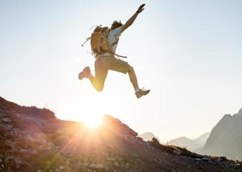 backpacker man sun jump happy