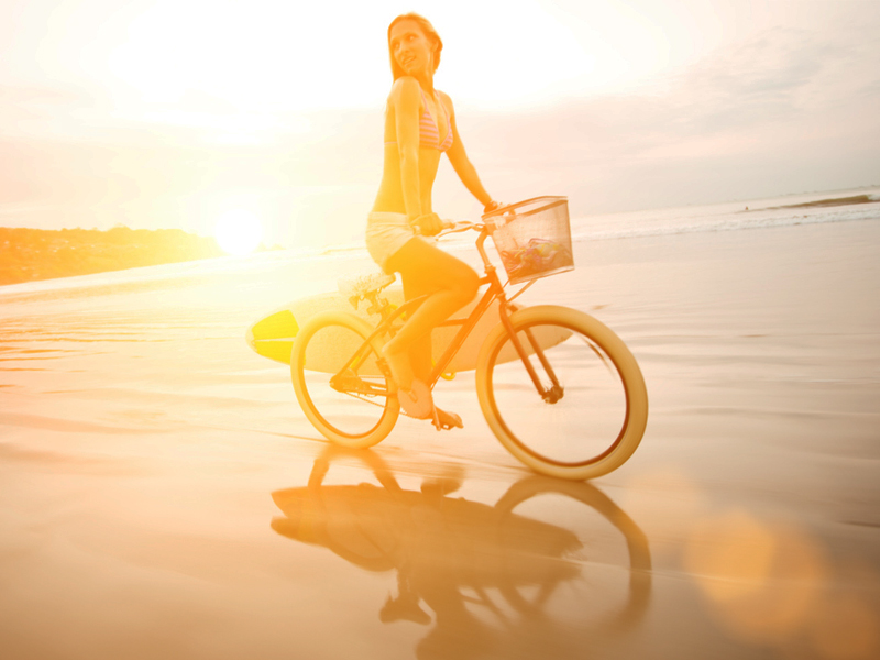 female cyclist no helmet beach
