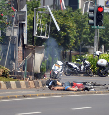 Bodies lie on the street next to a damaged police post in Jakarta.