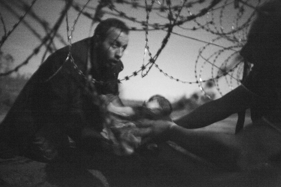 In Warren Richardson's photo, a man passes a baby through a fence at the Hungarian-Serbian border. Supplied: Warren Richardson/World Press Photo