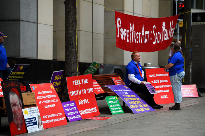 Demonstrators are seen with placards outside the commission in Sydney. Photo: AAP