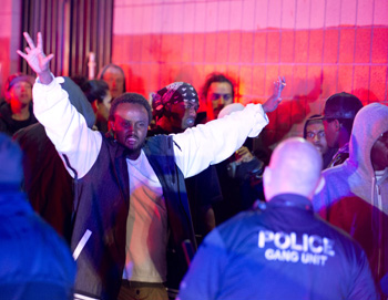 Police advance on an angry crowd following the shooting. Photo: AAP