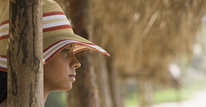 African woman in sunhat at beach