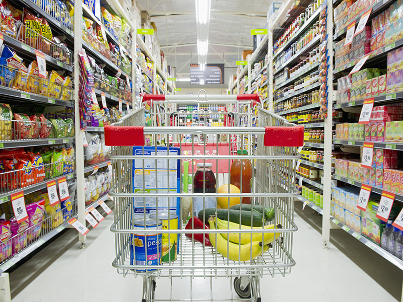 Shopping cart in grocery store aisle. trolley