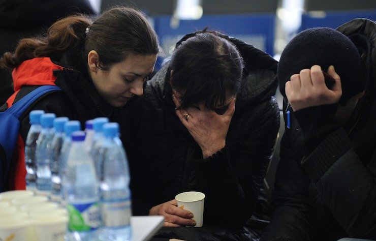 A Russian Emergency Situations Ministry employee, left, tries to comfort a relative of the plane crash victims at the Rostov-on-Don airport. Photo: AAP