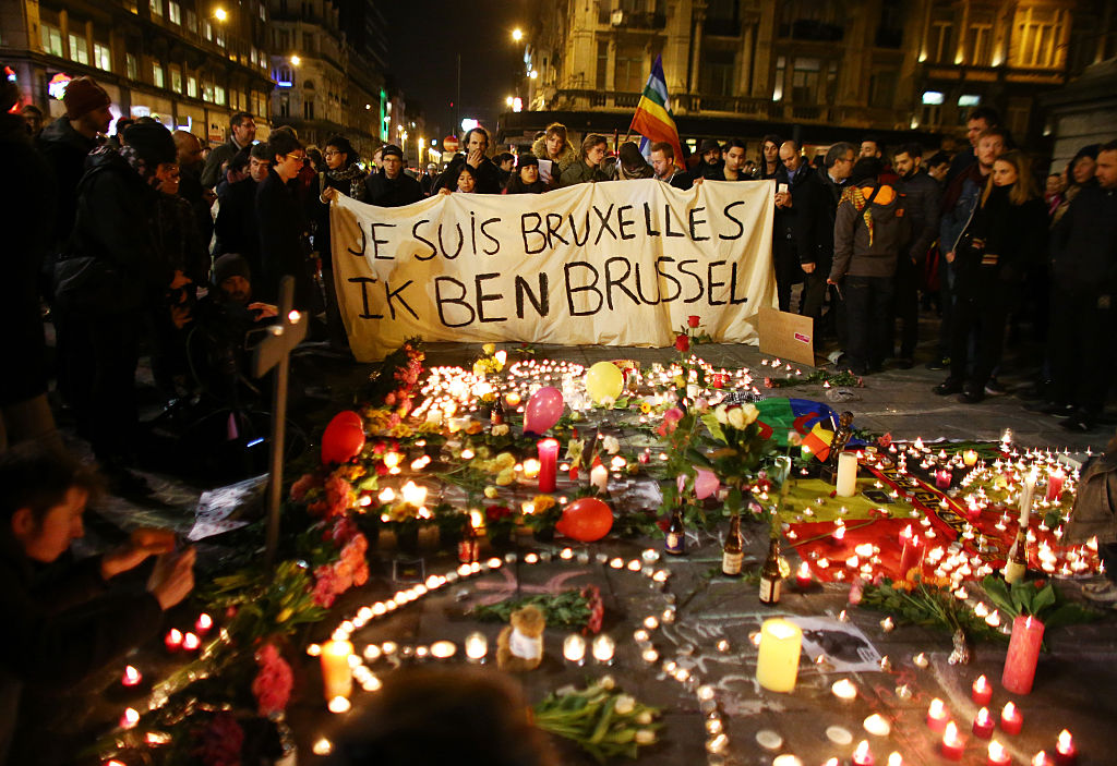 People hold up a banner as a mark of solidarity at the Place de la Bourse in Brussels.