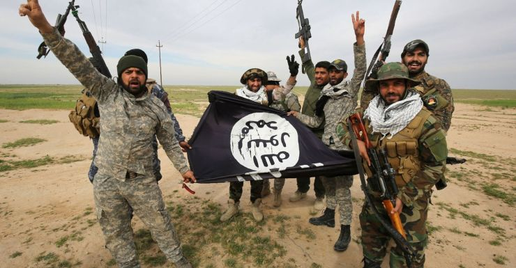 Iraqi Shiite fighters with a captured Islamic State flag.