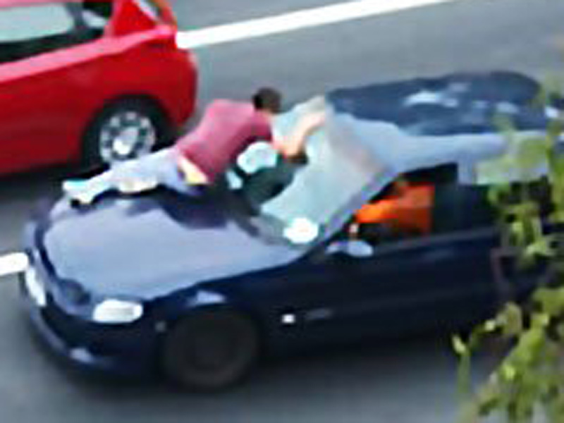 A man clings onto a moving car.