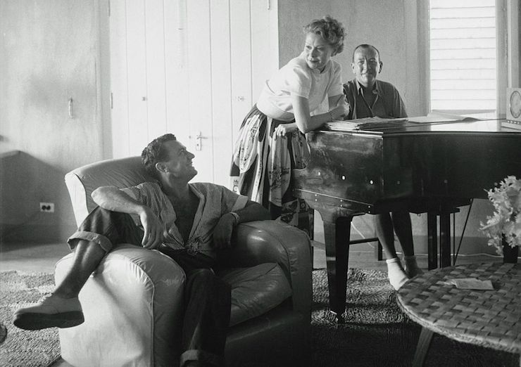 Noel Coward (at the piano) relaxes with friends in his home on Firefly. Photo: Getty
