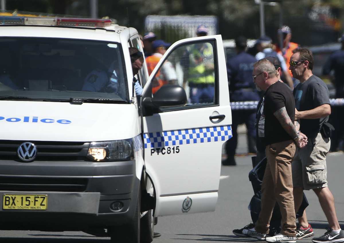 A man is led away from the scene by officers. He allegedly hindered police.Photo: AAP