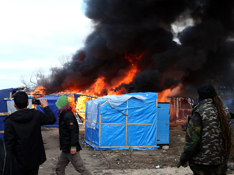 Migrants look on as a hut burns.