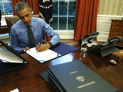 WASHINGTON, DC - DECEMBER 18: U.S. President Barack Obama signs one of 12 bills at his desk in the Oval Office at the White House December 18, 2015 in Washington, DC. Later today President Obama will travel to San Bernardino, California, to meet with families of the 14 victims of the recent mass shooting, before heading to Hawaii for Christmas vacation and return on January 3, 2016. (Photo by Mark Wilson/Getty Images)