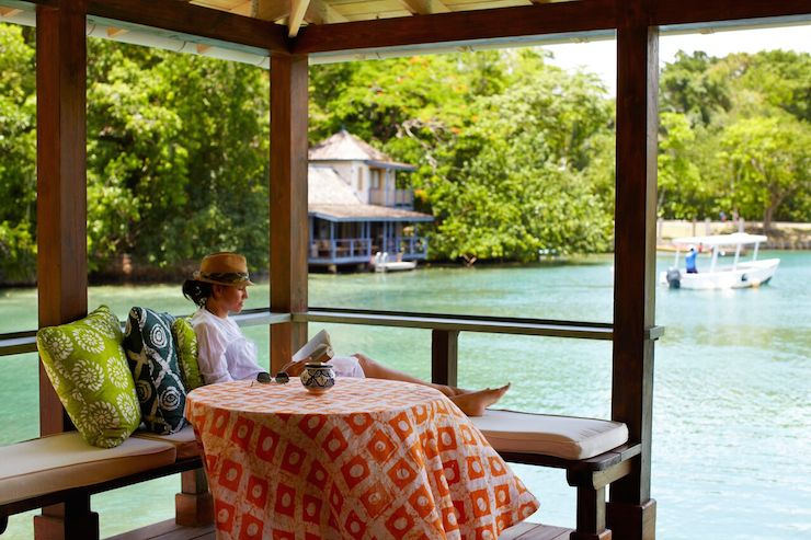 A guest at Goldeneye enjoys the views from the porch of the Lagoon Cottage. Photo: Goldeneye