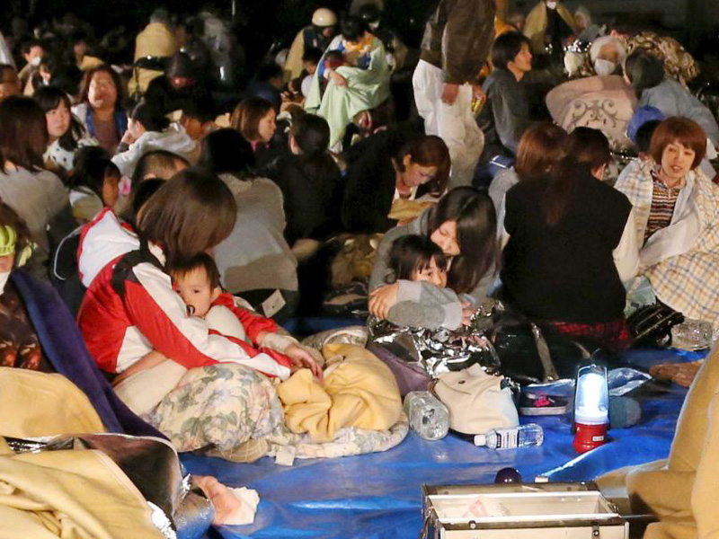 Evacuees gather in front of the town office building after escaping homes after the earthquake struck.