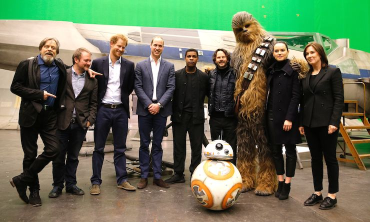 (L-R) US actor Mark Hamill, US director Rian Johnson, Britain's Prince Harry, Britain's Prince William, Duke of Cambridge, British actor John Boyega, Chewbacca and British actress Daisy Ridley pose during a tour of the Star Wars sets at Pinewood studios in Iver Heath, west of London on April 19, 2016. Photo: Getty