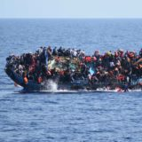 Asylum seekers try to jump just before their boat overturns off the Libyan coast.