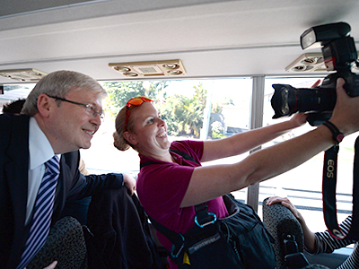 A photographer takes a picture of herself with Prime Minister Kevin Rudd while on the media bus in Brisbane, Tuesday, Aug. 6, 2013. The federal election will be held September 7. (AAP Image/Lukas Coch) NO ARCHIVING