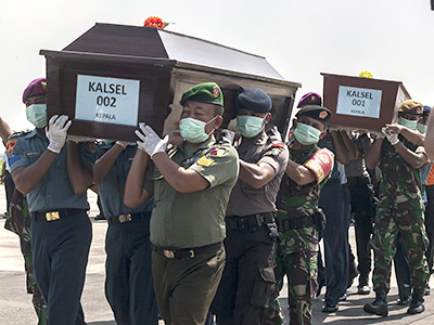Indonesian police and military personnel carry coffins with the remains of a passengers of the AirAsia flight 8501 in Surabaya, eastern Java island, on January 17, 2015. Indonesian divers again failed to reach the main body of an AirAsia plane that crashed into the sea last month with 162 people on board, as strong underwater currents hampered efforts. AFP PHOTO / Juni KRISWANTO (Photo credit should read JUNI KRISWANTO/AFP/Getty Images)
