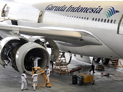 Aircraft technicians check the Rolls Royce engine of Garuda Indonesia's Airbus A330-300 aircraft at the company hangar in Jakarta airport on July 15, 2009. Indonesia, hoping for an upturn in European tourism, welcomed the EU's decision to remove four Indonesian airlines including crash-blighted Garuda Airlines from its aviation blacklist. Once reeling from a spate of deadly accidents, flag-carrier Garuda said it planned to resume flights to Europe as early as next year, and is also eyeing the lucrative US market. AFP PHOTO/ROMEO GACAD (Photo credit should read ROMEO GACAD/AFP/Getty Images)