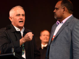 Prime Minister Malcolm Turnbull (left) speaks while Opposition Leader Bill Shorten (centre) and Indigenous Leader Michael Long (right) take part in the AFL's Long Walk to the MCG for the Dreamtime game Essendon play Richmond in Melbourne, Saturday, May, 28, 2016. (AAP Image/Tracey Nearmy) NO ARCHIVING