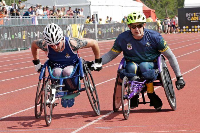Mark Urquhart helps US veteran Stephen Simmons across the finish line. Photo: ABC