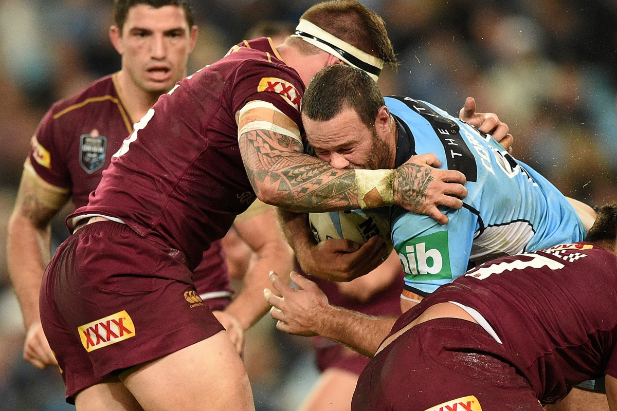 Boyd Cordner of the Blues is tackled by Josh McGuire of the Maroons.