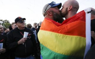 A couple shares a kiss as they embrace each other under a pride flag in the US.