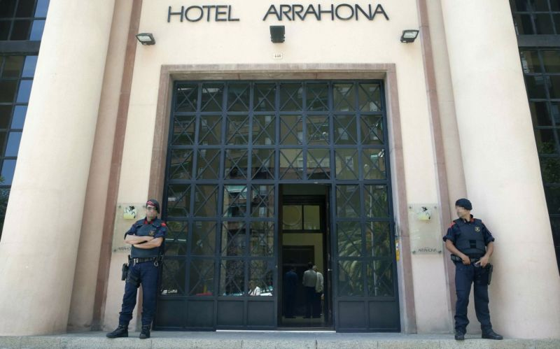 Police officers guard the entrance to the Arrahona hotel during a doping raid. Photo: AAP.