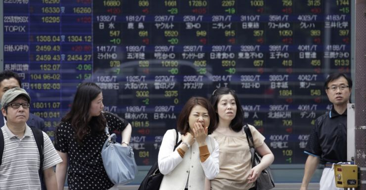 Pedestrians at a monitor displaying the Tokyo stock index.