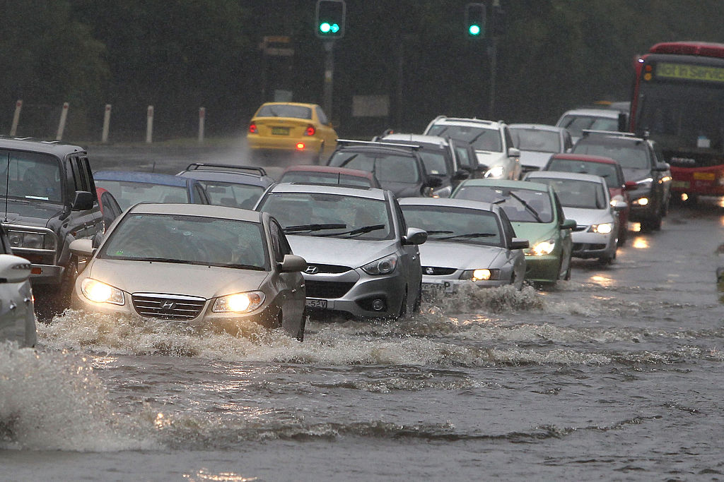 Cars drive through floodwaters on the New South Wales Central Coast.