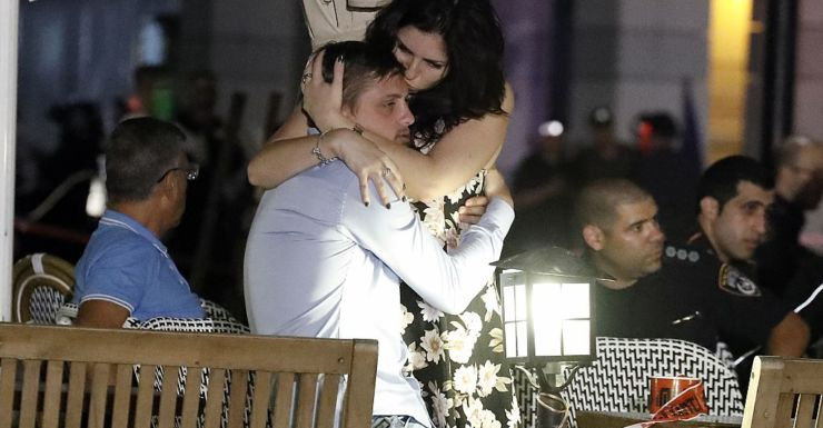 Israelis embrace after the shopping centre shooting attack.
