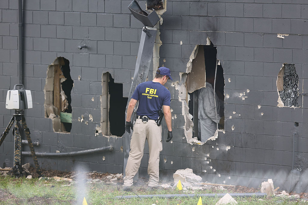 FBI agents investigate the damaged rear wall of the Pulse Nightclub. Photo: Getty.