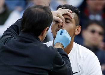 Nick Kyrgios of Australia receives medical attention during his men's singles match against Feliciano Lopez of Spain on day six of the Wimbledon Tennis Championships in London, Saturday, July 2, 2016. (AP Photo/Alastair Grant)