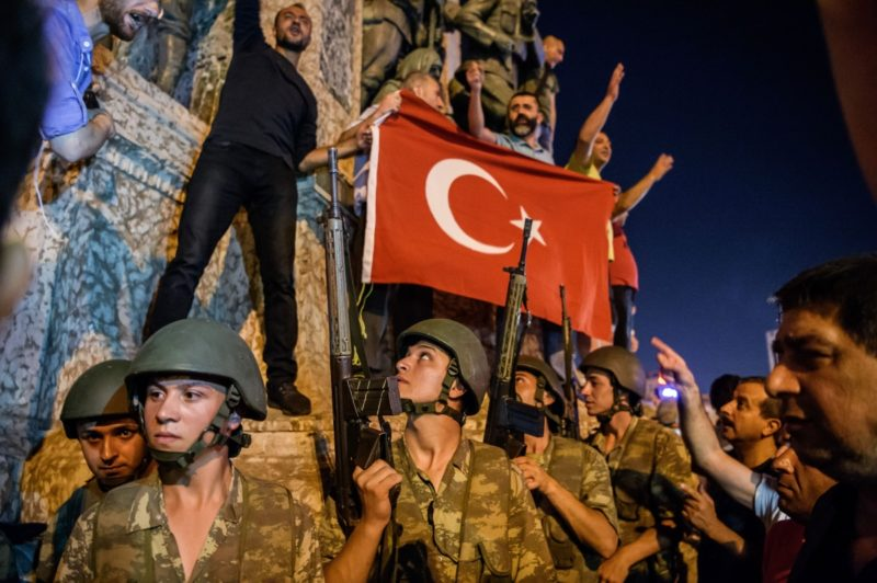 Turkish solders stand with weapons as people protest against the military coup in Istanbul.