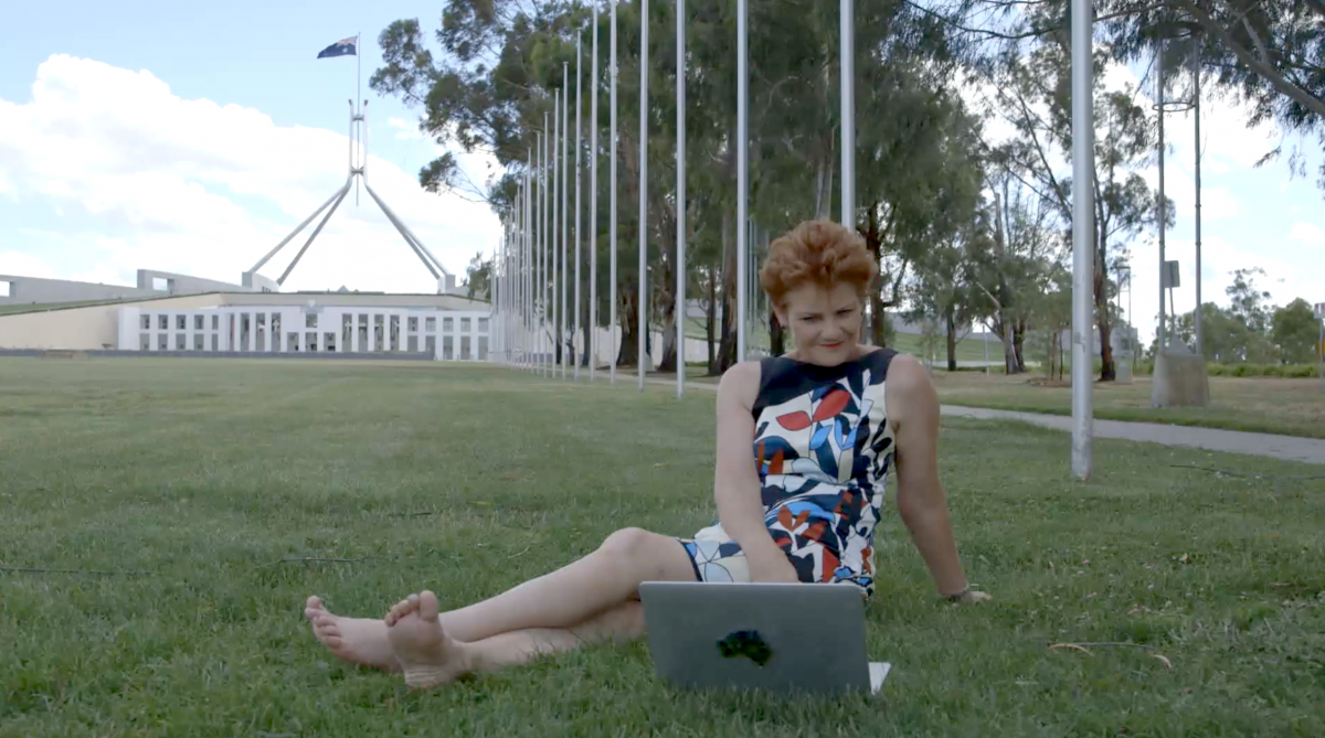 Hanson relaxes on the lawn outside Parliament House. Photo: SBS