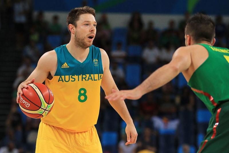 Matthew Dellavedova #8 of Australia looks to drive the ball against Mantas Kalnietis.