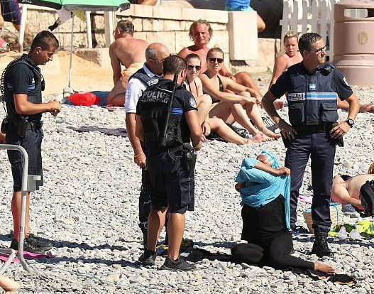 Armed police in Nice ask a woman to remove her burkini. Photo: Twitter.