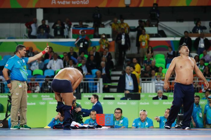 PHOTO: Coaches of Mongolia's wrestler Mandakhnaran Ganzorig strip in protest against the jury's decision. Photo: ABC