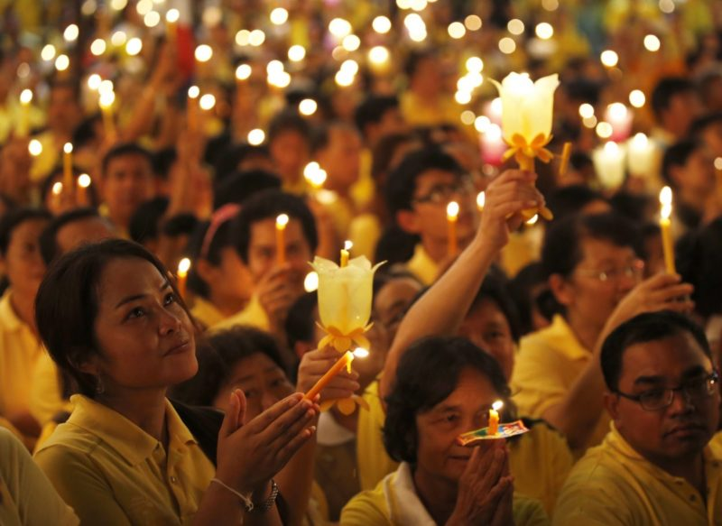Thai royalists light candles and sing anthems as they gather to celebrate the 87th birthday of King Bhumibol Adulyadej in 2014.