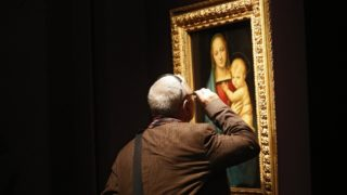 A man inspects Raphael's Madona Del Granduca at the Uffizi Gallery in Florence.