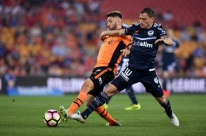 Melbourne's James Troisi and Roar's Brandon Borrello lunge for the ball.
